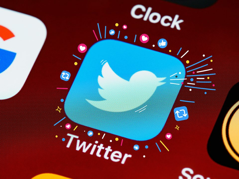 The Twitter icon on an iPhone, surrounded by retweet and like symbols