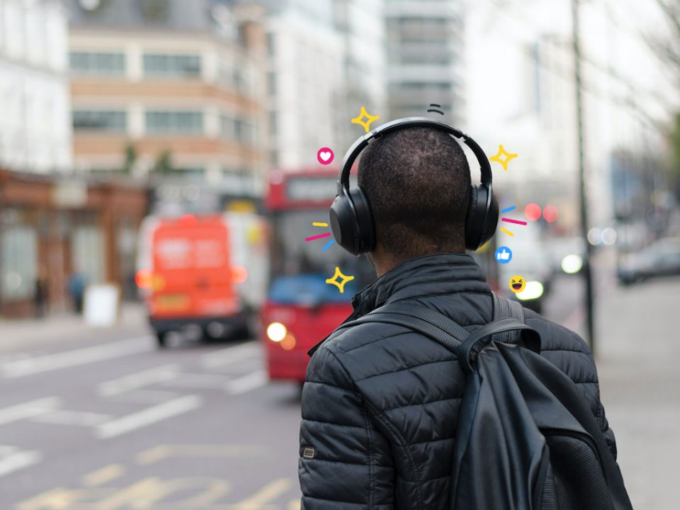 A man waiting for a bus in London wearing headphones