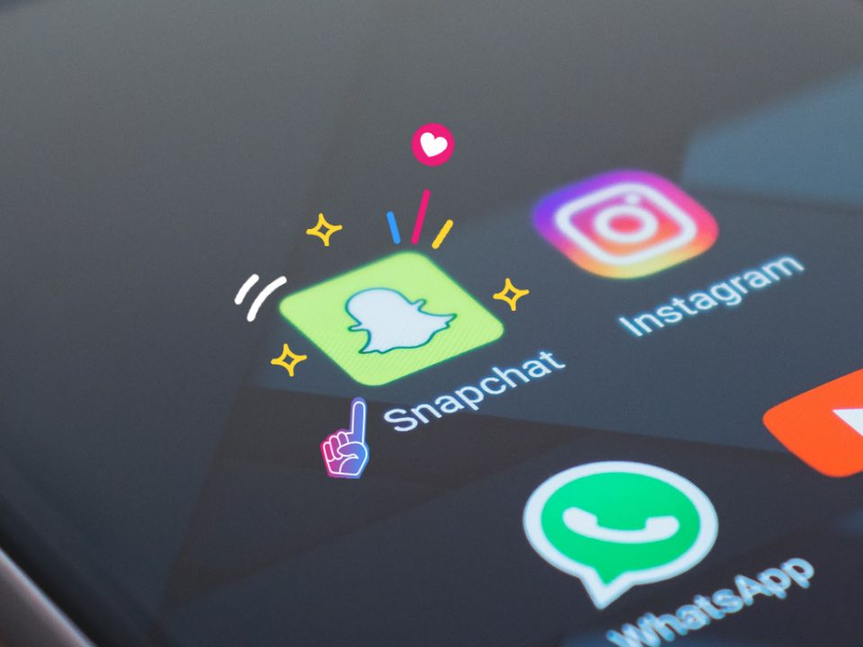 The Snapchat icon on an iPhone, surrounded by stars and colourful lines